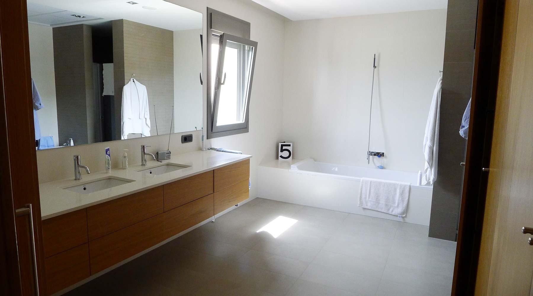 Cuarto de baño con lavabos en mueble de madera